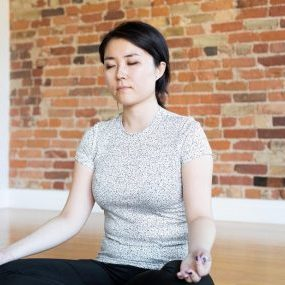 young-woman-meditating-in-front-of-brick-wall_925x